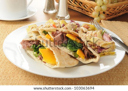 Roast beef in pita pockets with a Greek salad - stock photo