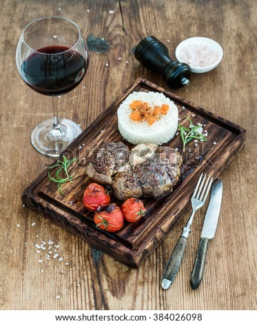 Roast beef Ossobuco with rice, vegetables and glass of wine on serving board over rustic wood background, selected focus - stock photo
