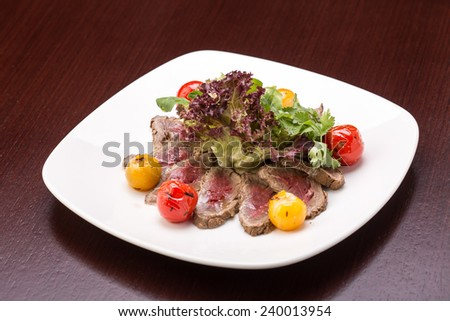 Roast beef salad with vegetables isolated on wooden table - stock photo