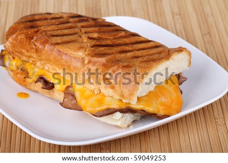 Roast beef sandwich covered with melted cheese on grilled French bread - stock photo