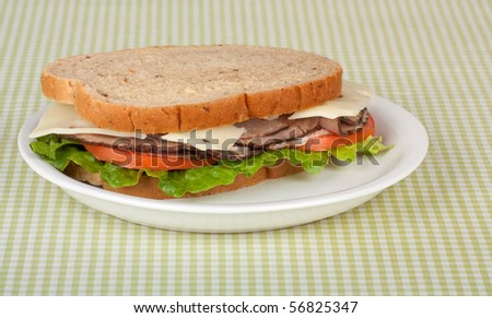 Roast beef sandwich on rye bread with swiss cheese, tomato, and lettuce - stock photo