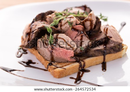 Roast beef sandwich with lettuce and liver paste on wooden background - stock photo