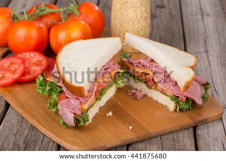 Roast beef sandwich with lettuce, tomato and cheese on a cutting board
