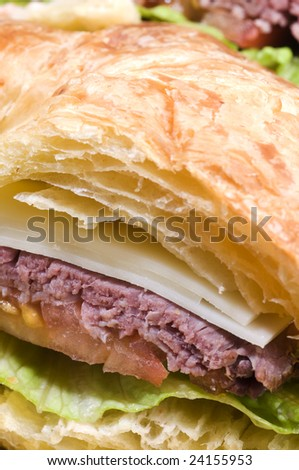 roast beef sandwich with swiss cheese on croissant french bread - stock photo