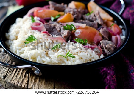 Roast beef with apples, red onions and garnished with rice - stock photo