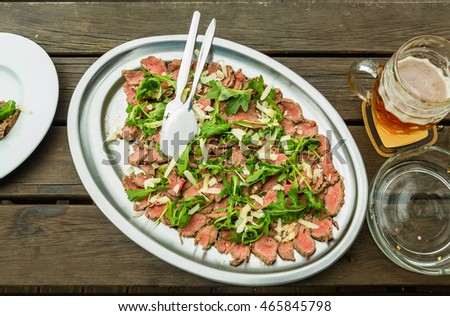 roast beef with arugula and Parmesan cheese served on a tray on a wooden base