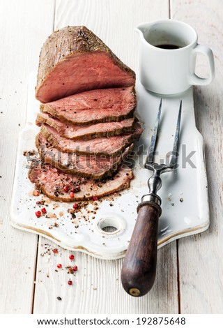Roast beef with sauce and meat fork on white wooden background - stock photo
