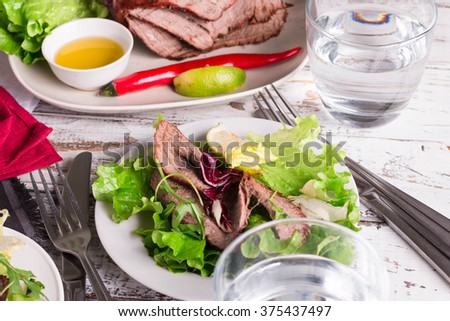 Roast Beef with sauce, healthy dinner plate. Green salad with meat, selective focus.