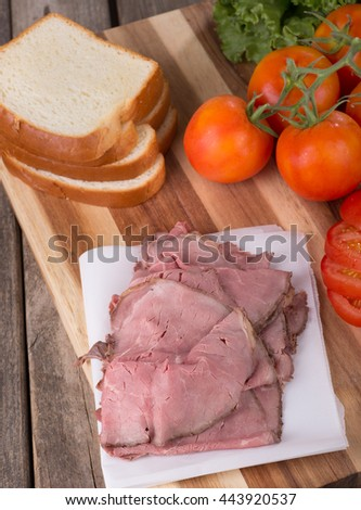 Roast beef with sliced bread, tomatoes and lettuce on a cutting board