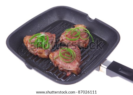 roast bloody beef fillet steaks on a grill plate with green leaves  isolated on white background