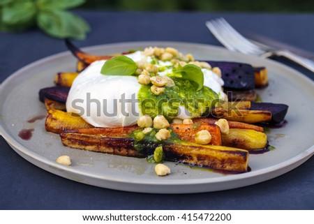 Roast carrots with burrata, pesto and hazelnuts - stock photo