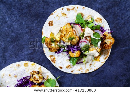 Roast cauliflower tacos with red cabbage, radish, tomatoes, spring onion, tahini sauce and chipotle sauce - stock photo