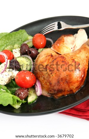 Roast chicken and Greek salad, on a black plate with red napkin.