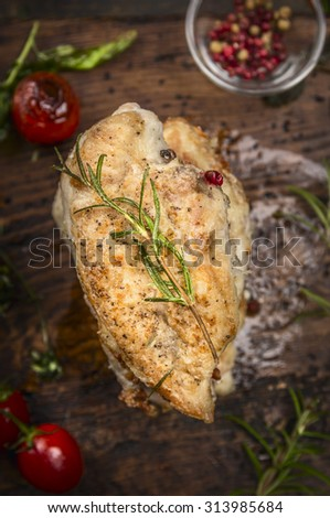 Roast chicken breast with Rosemary and vegetables on dark wooden background, top view, close up - stock photo