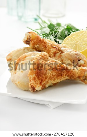 Roast chicken drumsticks or legs against a light, bright background with copy space availability. Lemon garnish with parsley herbs. Selective focus and shallow DOF. - stock photo