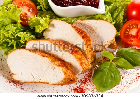 Roast chicken fillet and vegetables on white background  - stock photo