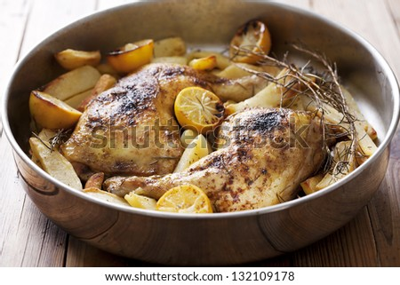 roast chicken legs,cooked with rosemary, lemon and potatoes - stock photo