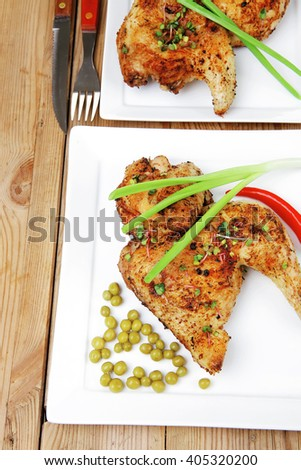 roast chicken : legs garnished with green peas , peppers , and cutlery on white plates over wooden table - stock photo