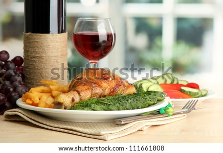 Roast chicken with french fries and cucumbers, glass of wine on  wooden table in cafe interior