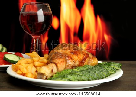 Roast chicken with french fries and cucumbers, glass of wine on wooden table  on fire background