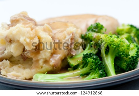 roast chicken with mashed potatoes, vegetables and smothered with creamy, rich gravy