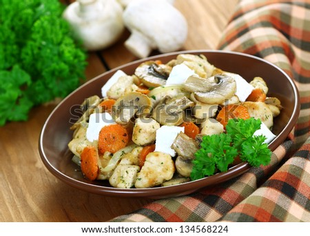 Roast chicken with mushrooms with cheese feta on a wooden table