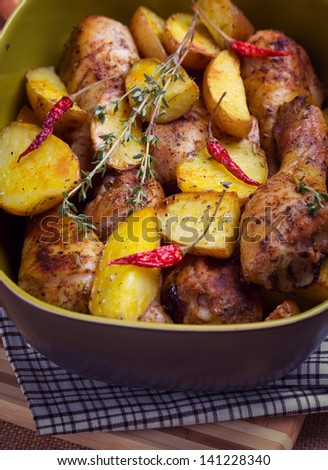 Roast chicken with potatoes - stock photo
