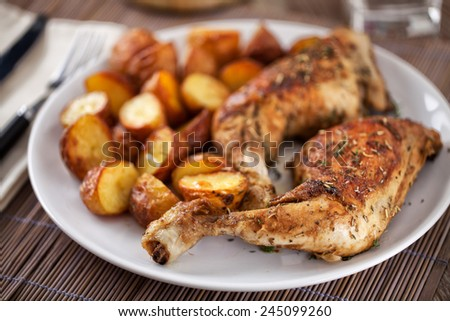 Roast chicken with potatoes on a plate - stock photo