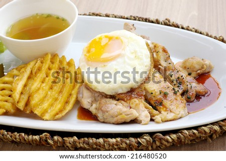 Roast chicken with red sauce and a fried egg. - stock photo