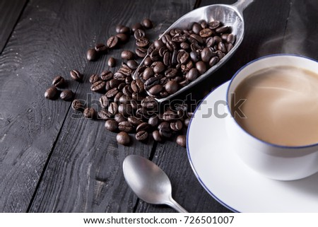 Roast coffee beans in metal scoop with sweet coffee in white cup foreground.