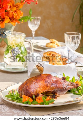 Roast duck on a vintage plate on summer time dinner table. Bouquet in vintage English vase. Bird shaped napkin rings. In bright natural light. Herbal tea in vintage jar. Roasted duck.