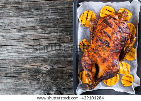 Roast duck with grilled orange slices on a parchment paper on a baking dish on an old dark wooden background, blank space left, top view - stock photo