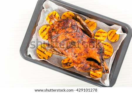 Roast duck with grilled orange slices on a parchment paper on a baking dish on an old white wooden background, blank space left, top view - stock photo