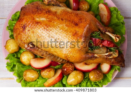 Roast duck with potato, apples, salad, thyme and rosemary. View From Above, Top Studio Shot