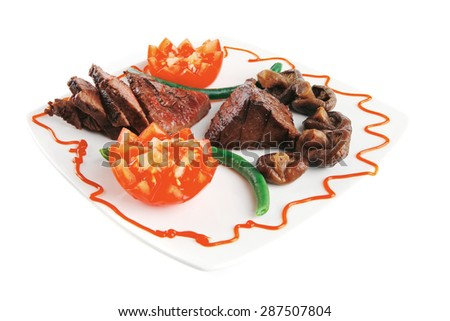 roast fillet mignon on a white ceramic plate with tomatoes - stock photo