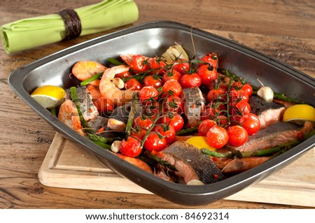 Roast fish fillet with prawns, asparagus and tomatoes