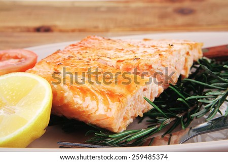 roast fish: hot grilled salmon over glass plate on over wooden table - stock photo