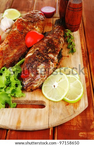roast golden fish served on wooden table with lemon tomatoes and salad