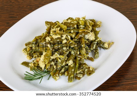 Roast green beans with egg served rosemary branch