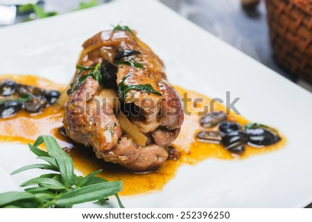 Roast lamb chops with black olives on a plate on a wooden table with decor in a restaurant - stock photo
