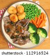 Roast lamb dinner with vefetables gravy and mint sauce. - stock photo