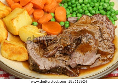 Roast lamb dinner with vegetables and gravy. - stock photo