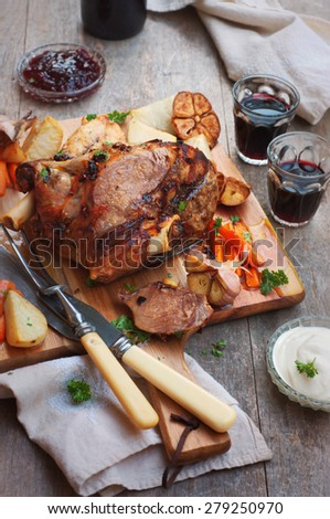 Roast leg of lamb with roasted potatoes and carrots on chopping board and rustic wooden background. selective focus - stock photo