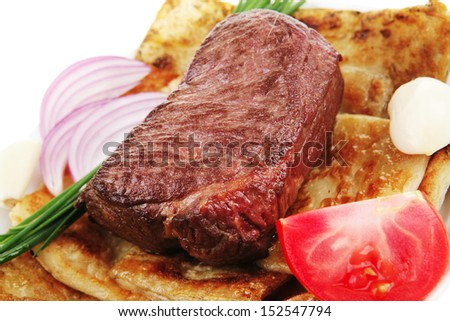 roast meat : beef ( lamb ) steak garnished with onion , tomatoes salad and chives isolated over white background - stock photo