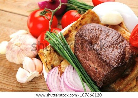 roast meat : beef ( lamb ) steak garnished with onion , tomatoes salad and chives, on wooden table