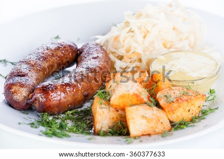 Roast meat sausages with potatoes and cabbage on a white background