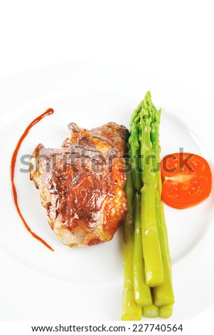 roast meat served with asparagus on white dish - stock photo