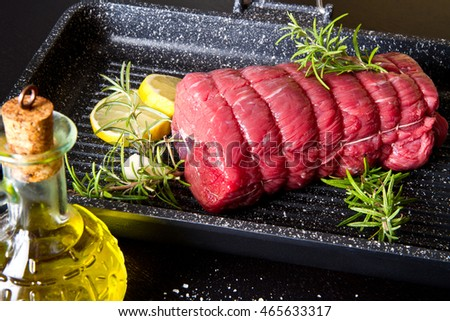 roast of beef with rosemary on plate pot on black