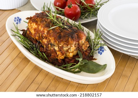 roast of veal  with rosemary and tomatoes on wooden table