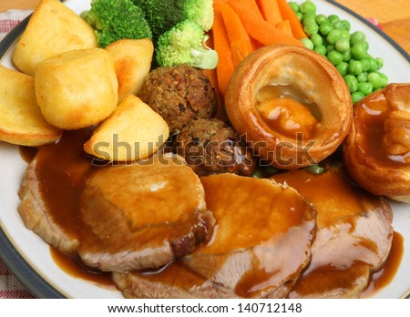 Roast pork Sunday dinner with vegetables and gravy.